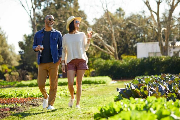 couple walking in the garden with drinks